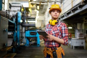 Female Engineering Intern Collecting Data in Factory